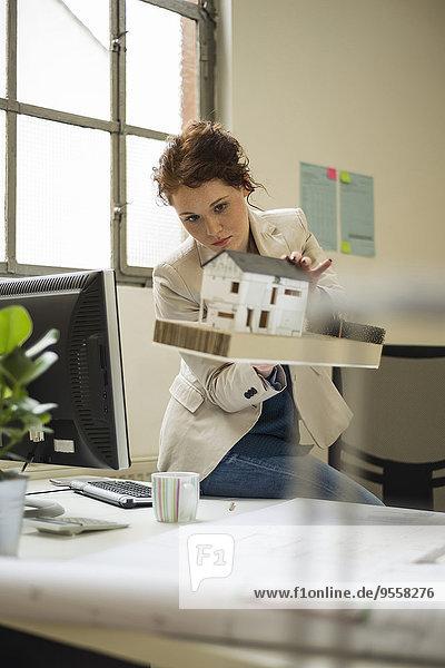 Junge Frau im Büro mit Architekturmodell