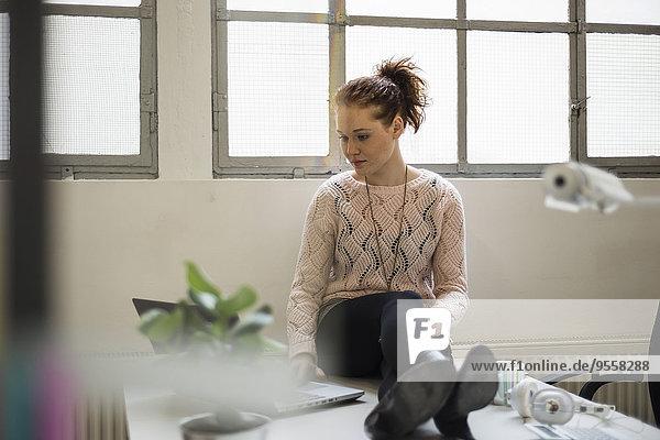 Junge Frau sitzt auf dem Schreibtisch mit Laptop