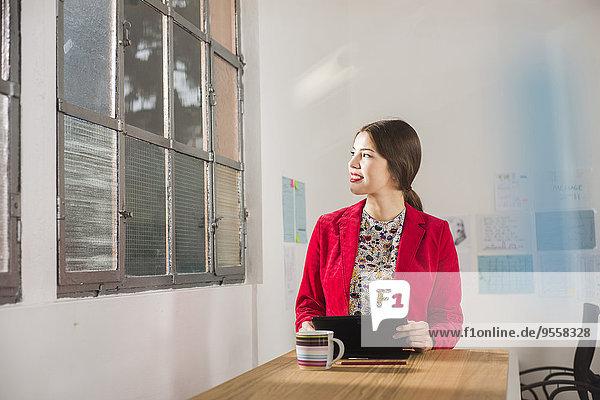Junge Geschäftsfrau mit digitalem Tablett im Büro