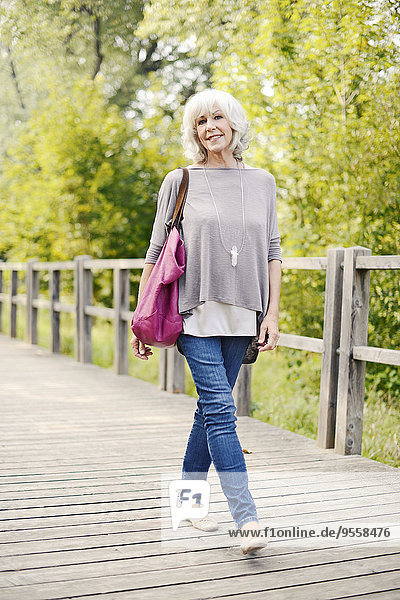 Portrait of smiling white haired senior woman walking on a wooden boardwalk