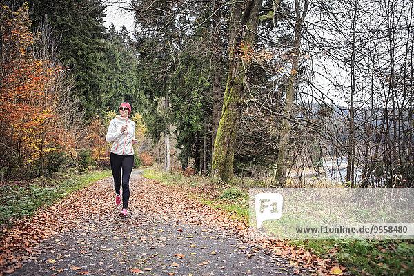 Deutschland  Thüringen  Frau läuft durch den Wald am See bei Alsbach