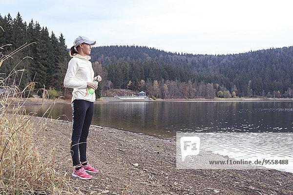 Joggerin mit Wasserflasche steht am Seeufer und genießt die Aussicht