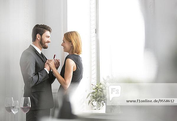 Elegantes Paar mit Verlobungsring im Restaurant