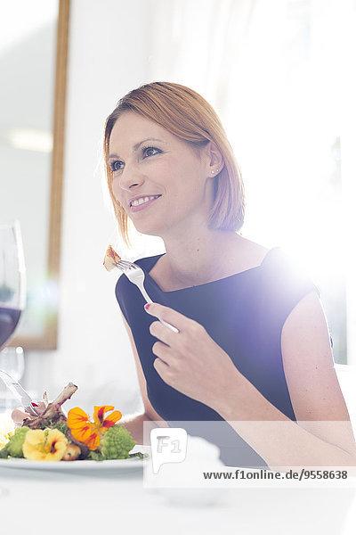 Elegante Frau beim Abendessen im Restaurant