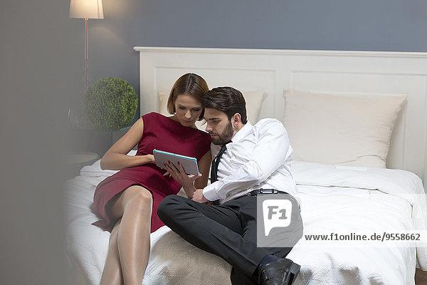 Elegantes Paar mit digitalem Tablett im Bett