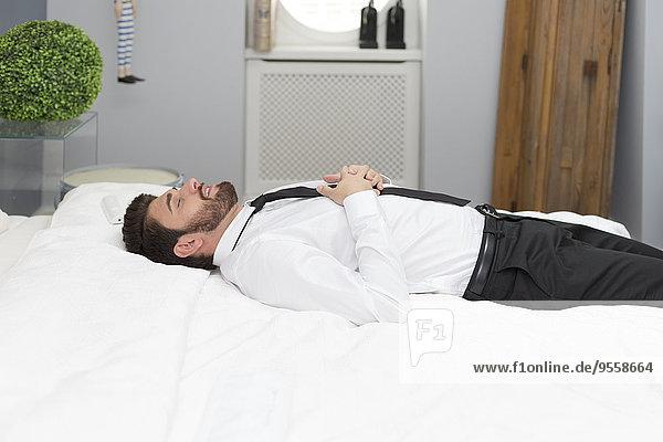 Mann im Hemd und Krawatte im Bett liegend