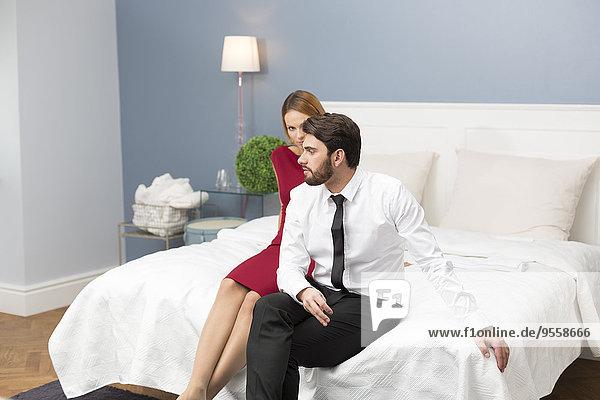 Elegantes Paar auf dem Bett sitzend