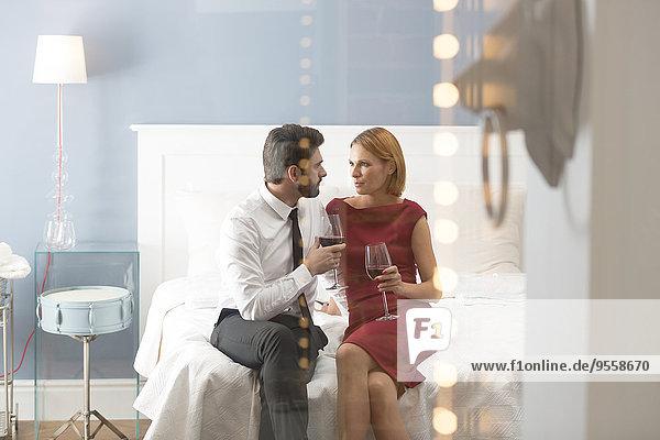 Liebespaar mit Weingläsern im Schlafzimmer