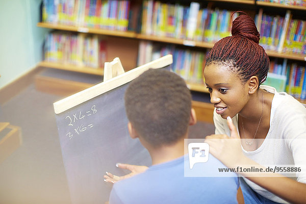 Junge Frau beim Rechnen mit dem Jungen in der Bibliothek