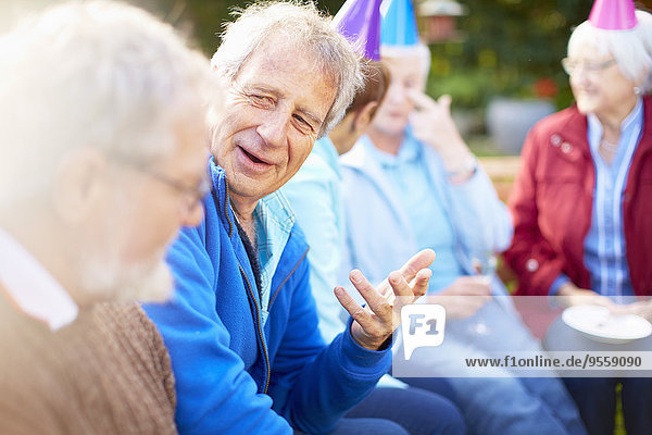 Seniorenfreunde auf einer Geburtstagsgartenparty