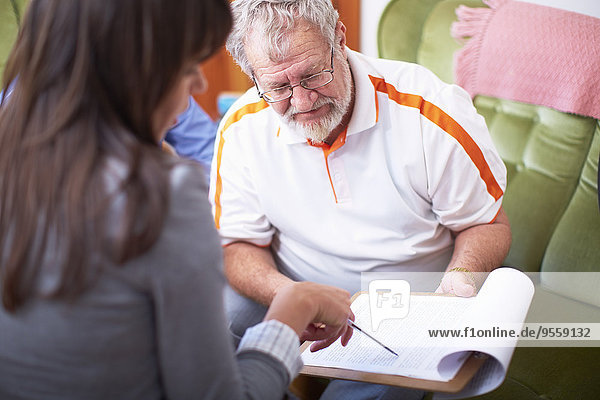 Woman explaining document to senior man