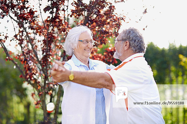 Seniorenpaar tanzt im Park