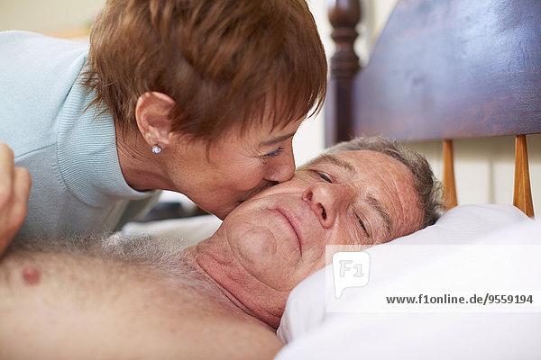 Seniorin küsst kranken Mann im Bett