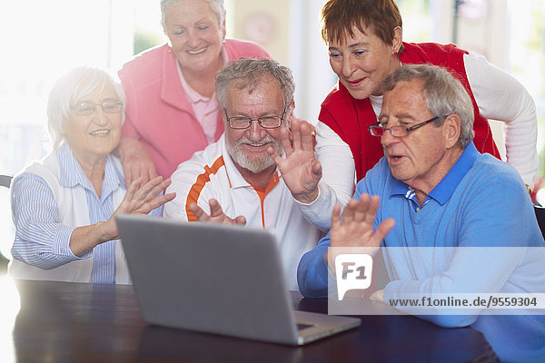 Seniorenfreunde bei einer Videokonferenz am Laptop