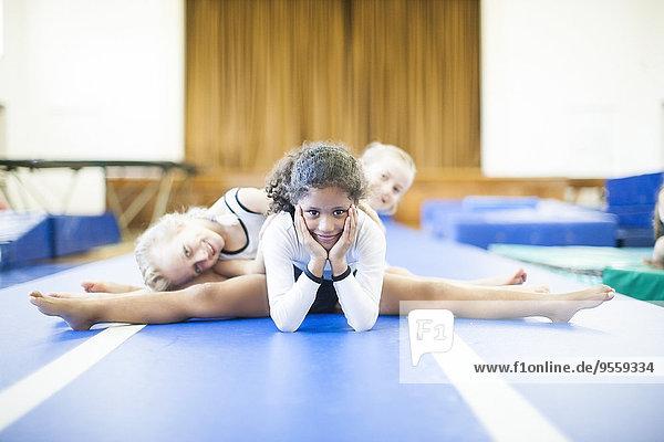 Drei Mädchen beim Turnen auf dem Boden