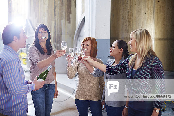 Group of people clinking wine glasses on shop floor