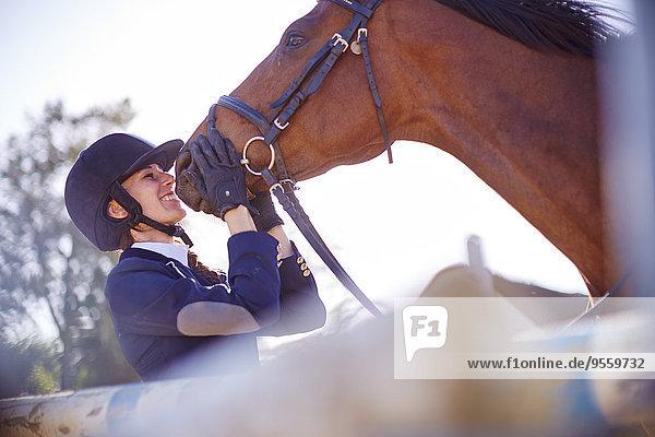 Lächelnde junge Frau mit Pferd im Parcours