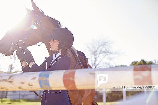 Junge Frau mit Pferd im Parcours