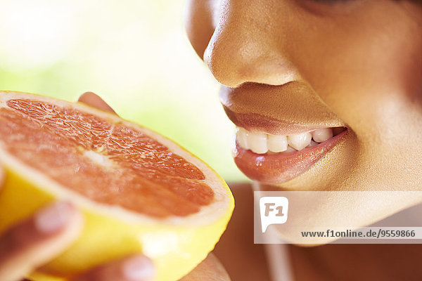 Lächelnde Frau hält die Hälfte der Grapefruit,  Nahaufnahme