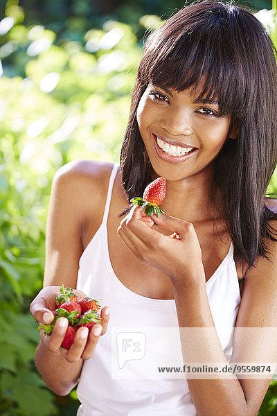 Porträt einer lächelnden Frau beim Erdbeeressen