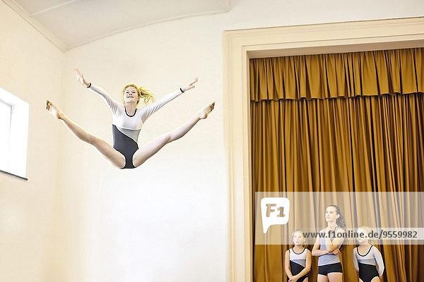 Mädchen im Gymnastik-Outfit beim Luftsprung mit drei Mädchen beim Zuschauen