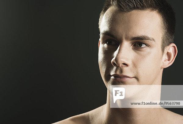 Portrait Mann sehen schwarz Hintergrund Close-up jung schießen Studioaufnahme Seitenansicht