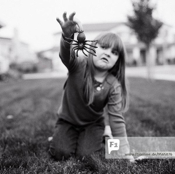 Ein Mädchen mit einer falschen Spinne.