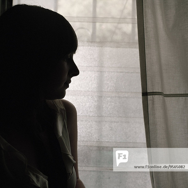 Eine Frau  die neben einem Fenster steht.