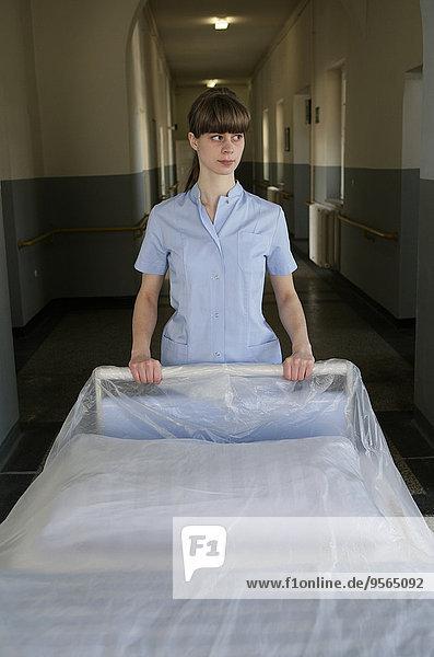 Eine Krankenschwester schiebt eine Krankenhausbahre in den Flur.