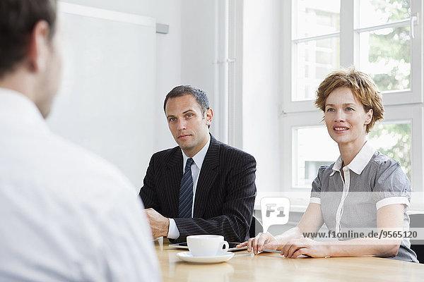 Geschäftsleute  die an einem Konferenztisch sitzen und eine Besprechung abhalten.