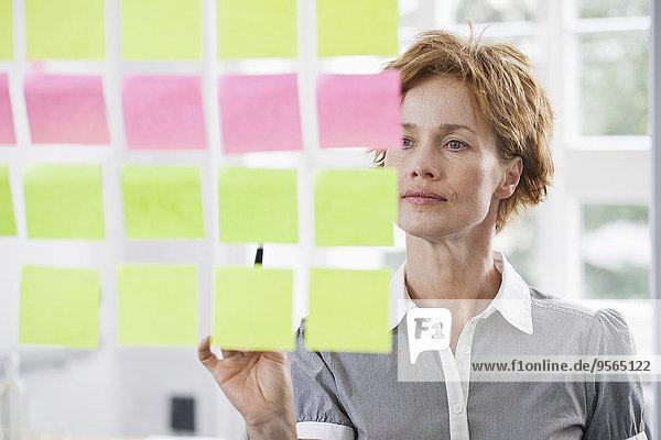 Eine Geschäftsfrau erwägt Reihen von Haftnotizen auf Glas