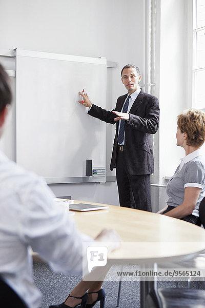 Ein Geschäftsmann  der ein Treffen leitet.