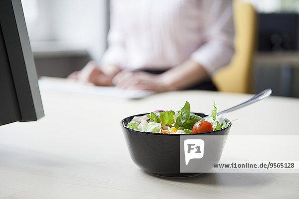 Ein Salat auf einem Schreibtisch  im Hintergrund eine Geschäftsfrau beim Tippen