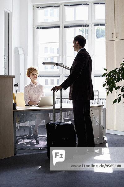 Ein reisender Geschäftsmann im Gespräch mit einer Geschäftsfrau am Schreibtisch