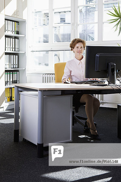 Eine Geschäftsfrau  die an einem Computer in einem Büro arbeitet.