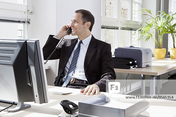 Ein Geschäftsmann  der in seinem Büro sitzt und telefoniert.