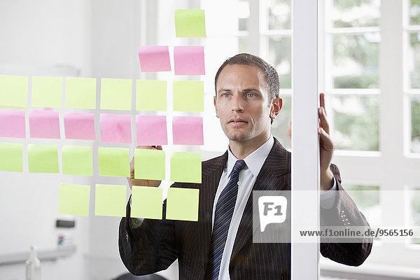 Ein Geschäftsmann  der Reihen von Haftnotizen auf Glas betrachtet.