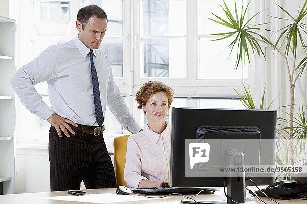 Ein Geschäftsmann  der einer Geschäftsfrau hilft  die an einem Computer sitzt.