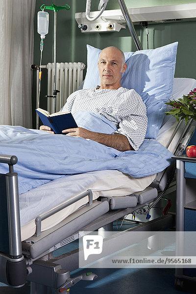 Porträt eines Mannes mit einem Buch im Krankenhausbett