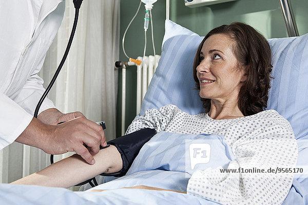 Ein Mann  der den Blutdruck einer Patientin überprüft.