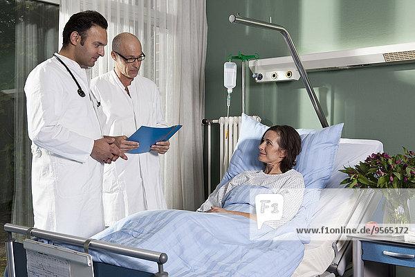Zwei Ärzte neben einer Patientin auf einer Krankenstation