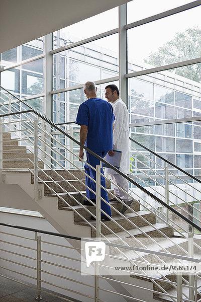 Medizinisches Personal  das eine Treppe in einem Krankenhaus hinaufgeht.