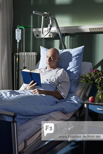 Ein Mann  der ein Buch in einem Krankenhausbett liest.