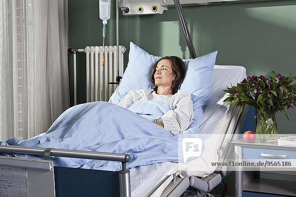 Eine Frau  die in einem Krankenhausbett liegt.