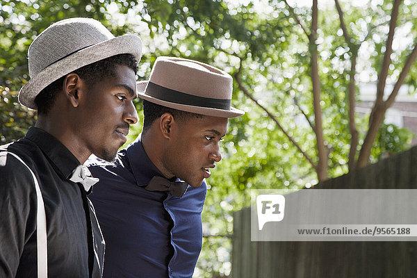 Zwei junge schwarze Männer mit Fliege und Hut  die weggucken.