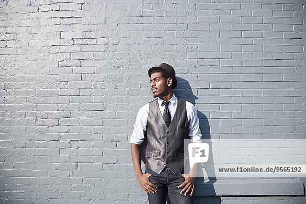 Ein junger schwarzer Mann  der sich an eine Ziegelmauer lehnt.
