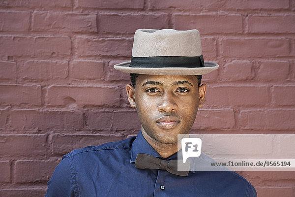 Ein junger schwarzer Mann mit Fliege und Hut  Nahaufnahme