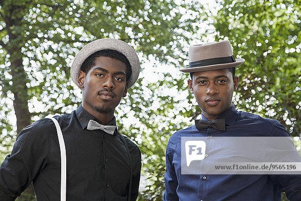 Zwei hübsche junge schwarze Männer mit Fliege und Hut.