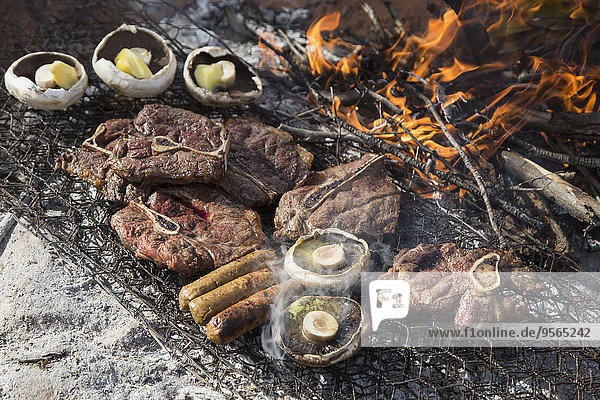 Großer Blickwinkel auf Fleisch und Champignons beim Grillen