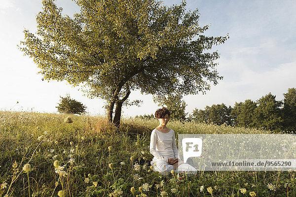 Frau meditiert auf grasbewachsenem Feld
